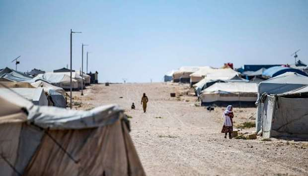 People walk past tents in the Kurdish-run al-Hol camp in the al-Hasakeh governorate in northeastern