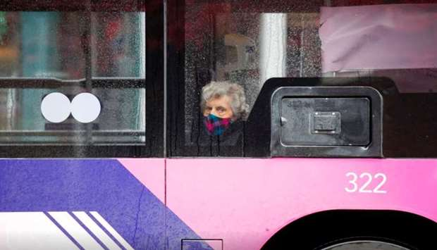 A woman wearing a face mask looks out from a window of a bus, following the outbreak of the coronavi