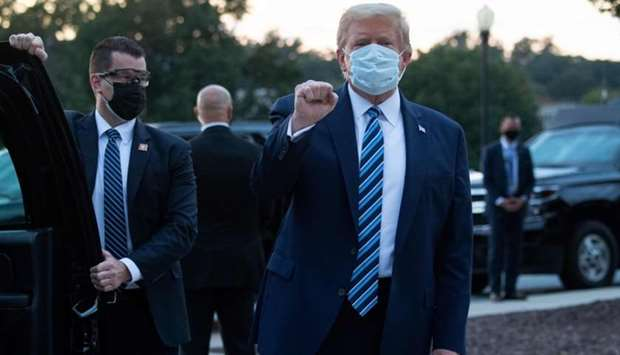 In this file photo taken on October 05, 2020 US President Donald Trump pumps his fist as he leaves W