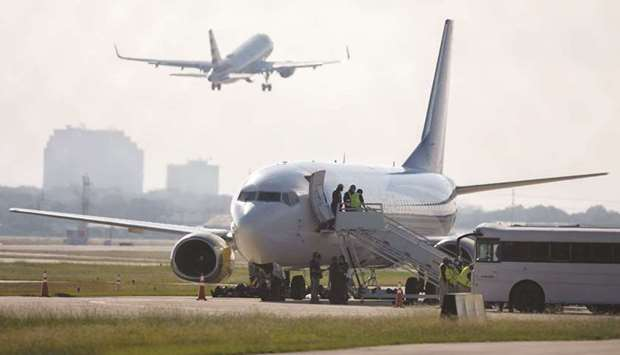 SPOTLIGHT: An airplane chartered to transport people to Haiti prepares to board passengers at the Sa