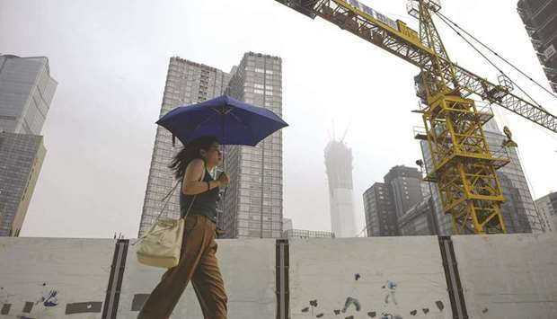 A woman holding an umbrella walks past a construction site in Beijing (file). The $5tn property sect