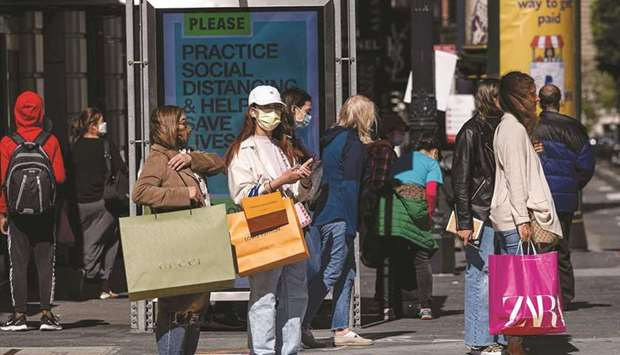 People carry shopping bags while waiting to cross Geary Street in San Francisco. US consumer prices