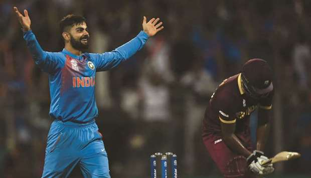 In this file photo taken on March 31, 2016, India's Virat Kohli celebrates after taking the wicket o