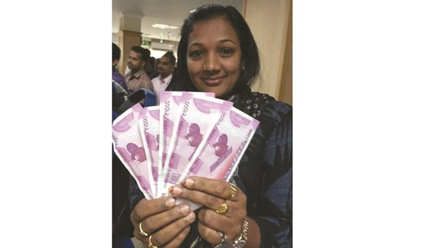 A woman displays new Rs2,000 notes as she poses outside a bank in Thiruvananthapuram yesterday.