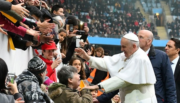 Pope Francis (C) shakes hands with wellwishers as he arrives at the Swedenbank Stadion