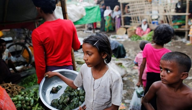 A girl sells food at the internally displaced person's camp for Rohingya people outside Sittwe in th