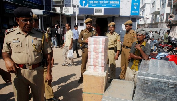 New 2000 Indian rupee banknotes are pictured outside a bank as policemen stand guard