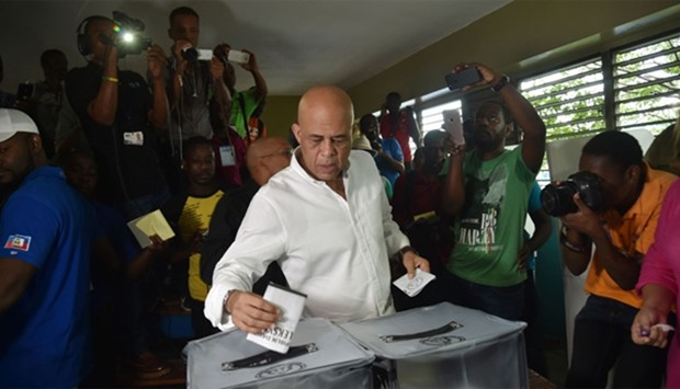 Former Haitian President Michel Martelly casts his ballot at a polling station