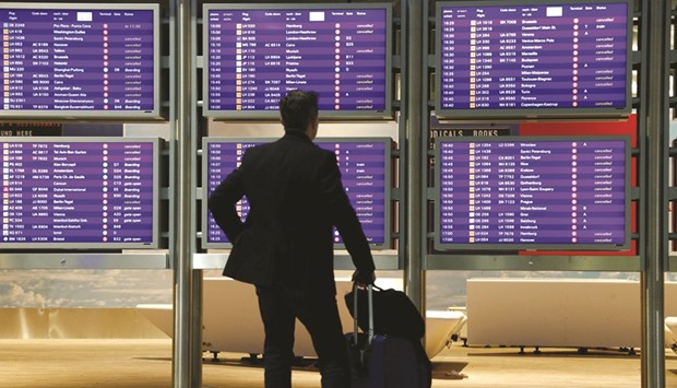 A flight passenger stands before an information board that shows most Lufthansa flights as cancelled
