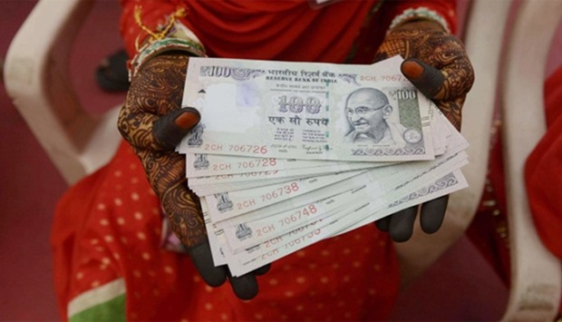 Indian bride poses for a photograph holding cash
