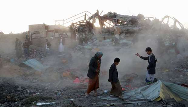 People walk at the site of an air strike in the northwestern city of Saada, Yemen