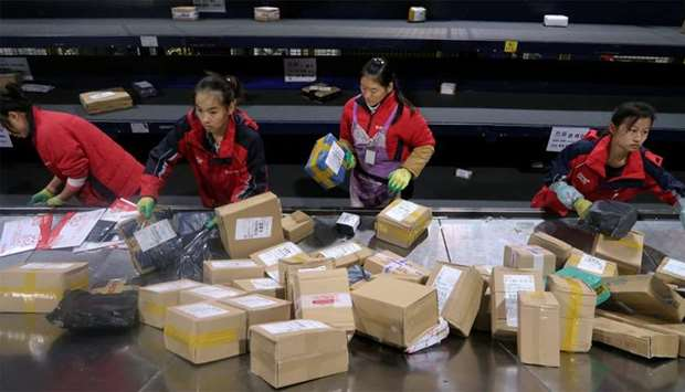 Employees sort packages on a conveyor belt network at a warehouse in Shanghai