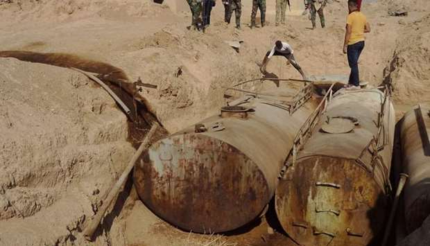 Iraqi forces unearth containers used by Islamic State group to store oil, near the former al bakara