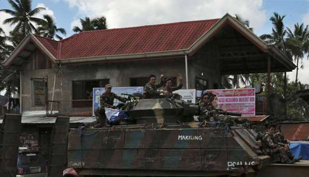 Soldiers wave while atop of the tank after the send-off ceremony ending their combat duty against pr