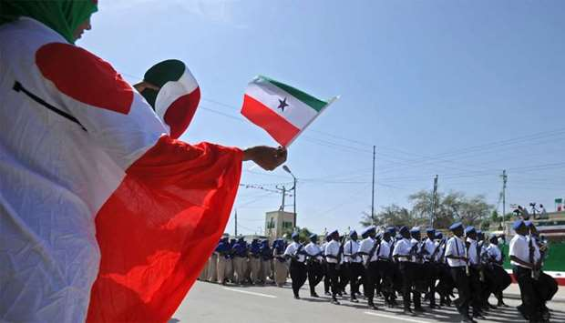 A woman waving a flag as soldiers and other military personnel of Somalia's breakaway territory of S