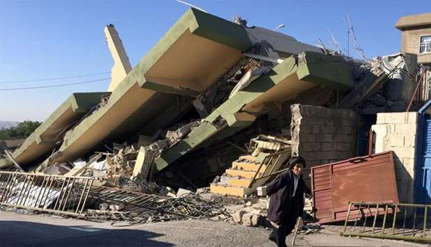 A man walks past a damaged building following an earthquake in Darbandikhan