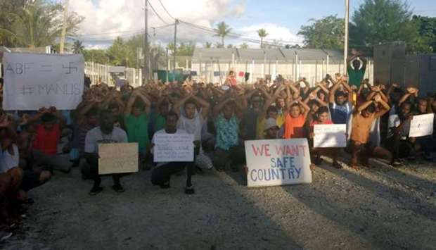 Asylum seekers hold placards in protest to moving to another centre on Manus island