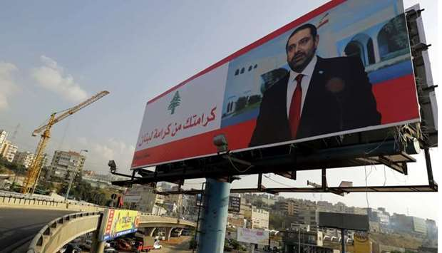 "A poster of Lebanese Prime Minister Saad Hariri is seen on a giant billboard that reads in Arabic ""Y"