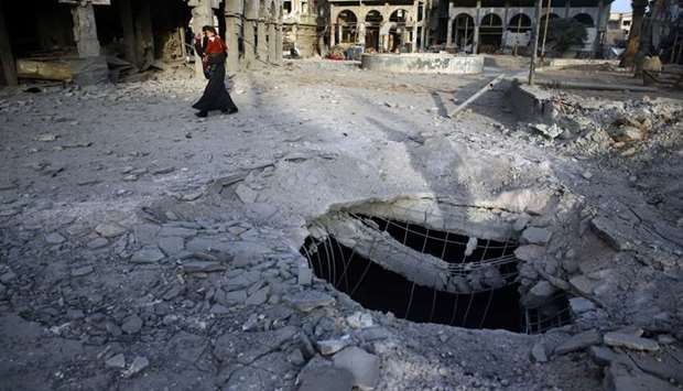 A Syrian woman walks past damaged buildings in Douma, in the eastern Damascus suburb of Ghouta, Syri