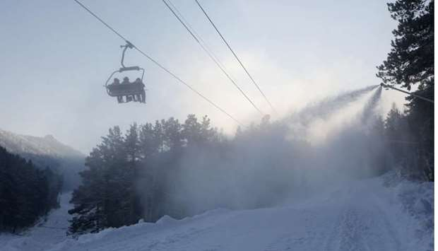 Employees use a chairlift as a snowmaking machine sprays artificial snow