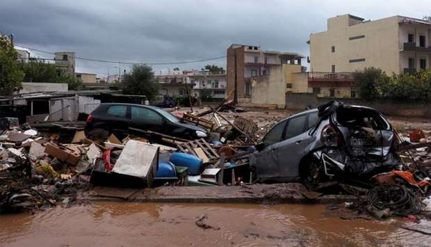 Destroyed cars are seen on a muddy street following flash floods which hit areas west of Athens