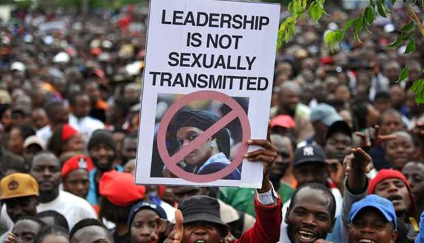 People hold an anti-Grace Mugabe placard during a demonstration demanding the resignation of Zimbabw