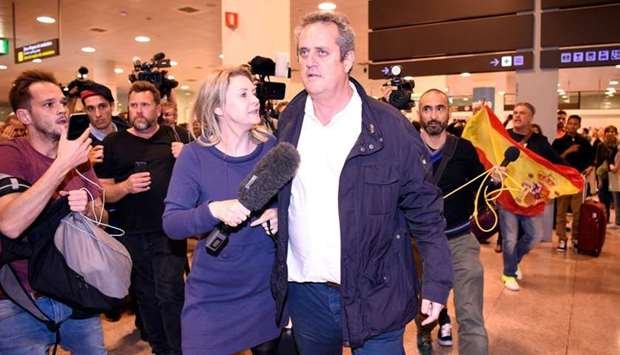 Catalan dismissed Interior chief Joaquim Forn (C) is followed by journalists as people with Spanish