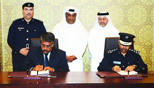 Brigadier Mohamed Ahmed al-Ateeq and Suresh Kumar, manager of the Singapore-based company, sign the