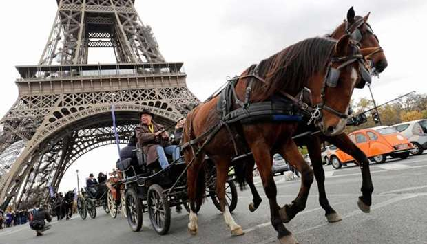 A man drives a carriage during the  parade at the Eiffel Tower in Paris