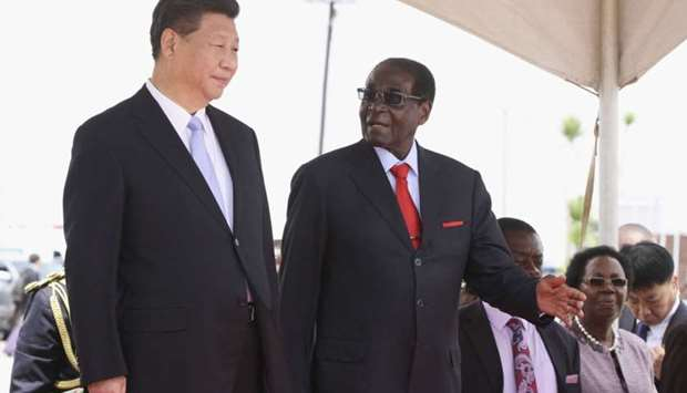 Chinese President Xi Jinping talks with Zimbabwean President Robert Mugabe on arrival for a state vi