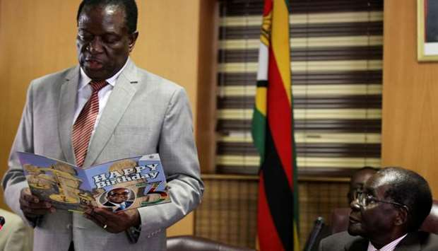 Zimbabwe's President Robert Mugabe looks on as his deputy Emmerson Mnangagwa reads a card during Mug