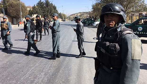 Afghan security forces stand guard near the site of a suicide attack