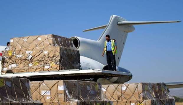A technician unloads doses of vaccines from a plane after it landed in the rebel-held Yemeni capital