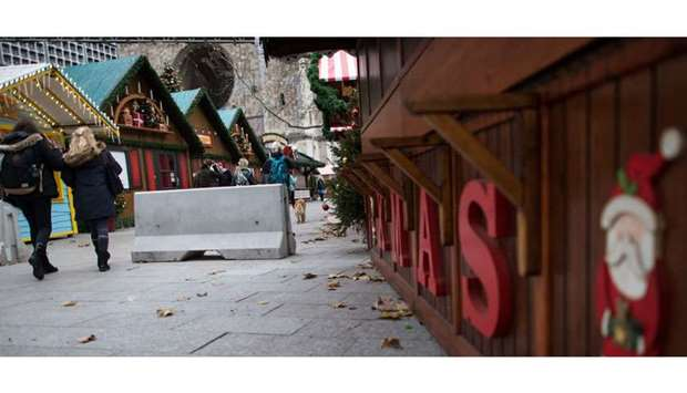 People walk past concrete barriers as preparations are under way for a Christmas market in front of