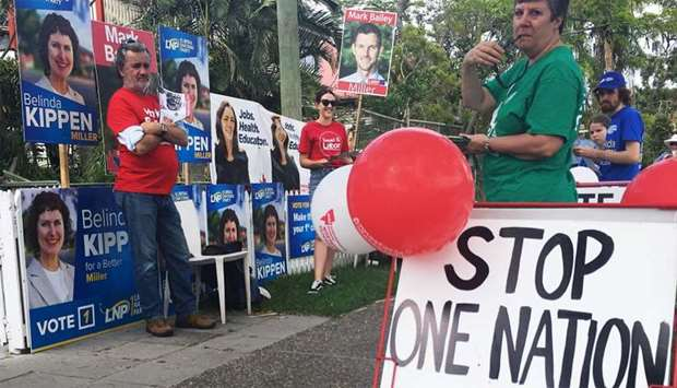 """Voters stand by a """"stop One Nation - vote Labor"""" sign in Graceville, near Brisbane"""