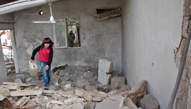 A Syrian child runs through the rubble following a reported shelling by Syrian government forces in