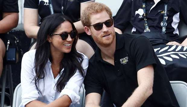 Britain's Prince Harry (R) sits with  actress Meghan Markle