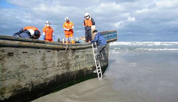 Coast guard officers inspecting a battered wooden boat where eight bodies were found inside at a bea