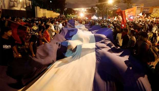Supporters of Nasralla hold a Honduran flag while they wait for the official presidential election r
