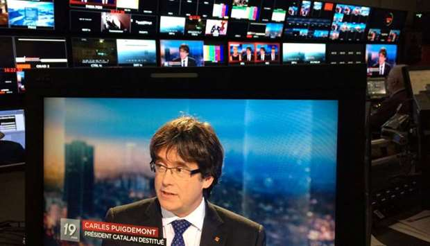Ousted Catalan President Carles Puigdemont appears on a monitor during a live TV interview at the Be