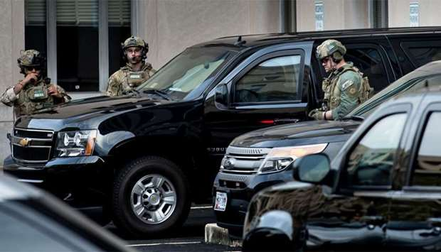 US Marshals wait to company an armored vehicle with Mustafa al-Imam as it leaves after a hearing at