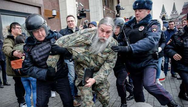 Russian riot police detain an opposition activist during a protest rally in central Moscow