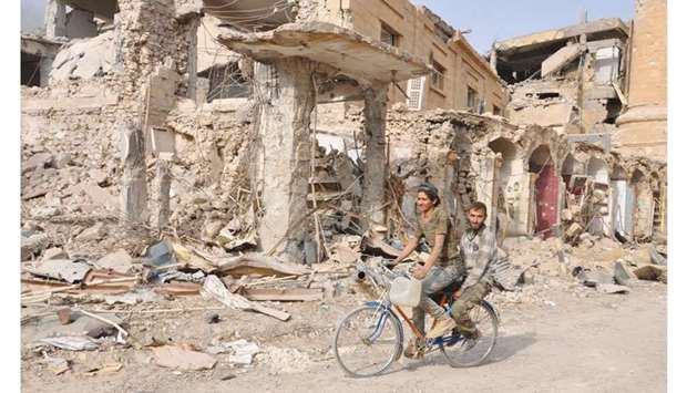 Men ride a bicycle in the eastern Syrian city of Deir Ezzor during a military operation by governmen