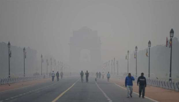 People walk early in the morning as smog covers India Gate war memorial in New Delhi