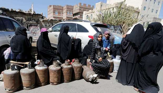 Women wait to fill up cooking gas cylinders outside a gas station amid supply shortage in Sanaa, Yem