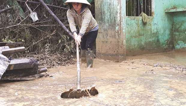A woman clears mud in a village in Quang Nam yesterday after the area was flooded by rains brought b