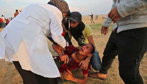 A wounded protester is evacuated during clashes near the border between Israel and Khan Yunis in the