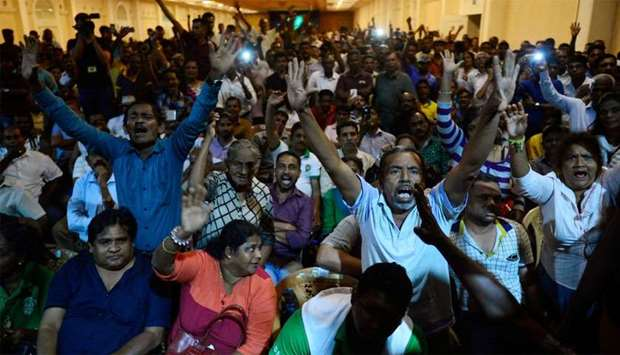 Supporters of ousted Sri Lanka's Prime Minister Ranil Wickremesinghe shout slogans as they gather at