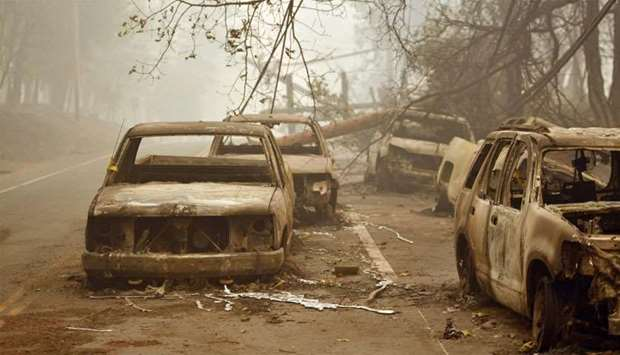 Burnt out vehicles are seen on the side of the road in Paradise, California