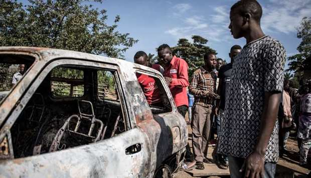 Congolese men look on at a car which has hit by a mortar, after an alleged attack by the Allied Demo
